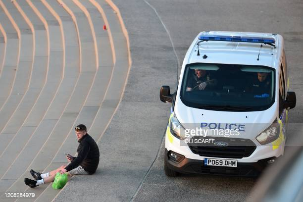 A man is spoken to by police in Blackpool northwest England on March 26 2020 The coronavirus outbreak and resulting lockdown of billions of people...