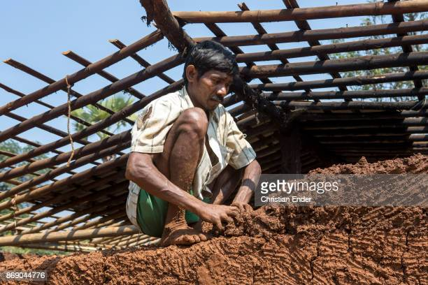 A man is squatting on a wall while he builds a house made from loam in a rural area about 300 Kilometer from Kolkata