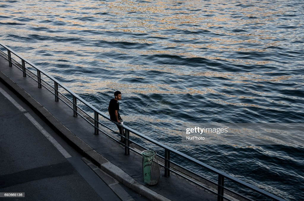 A man is standing and looking to the Seine river in Paris. People used the first days of the summer for walking around the French capital of Paris. The temperature of the weather is about 25 celsius degrees Paris, France on June 04, 2017