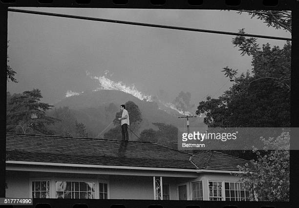 A man is standing atop his roof with a hose as he attempts to wet it down before the engulfing fire in the distance approaches