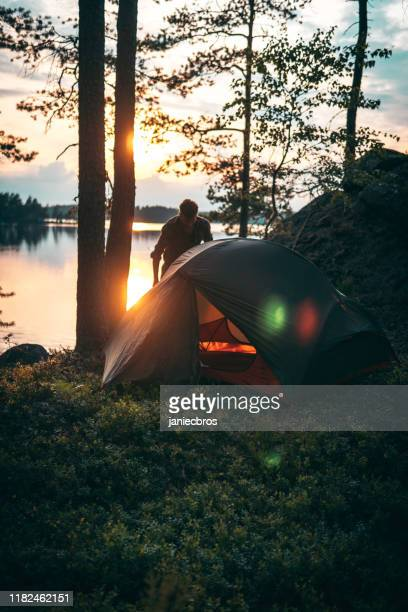 man is standing next to the tent standing in the forest - sweden stock pictures, royalty-free photos & images