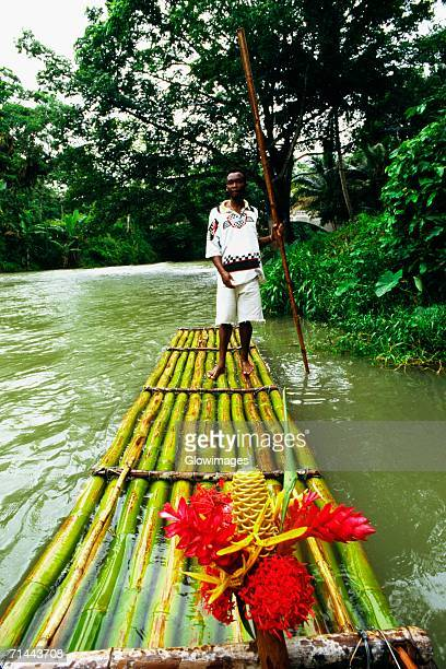 A man is standing on a bamboo raft floating down the Martha Brae River, Jamaica