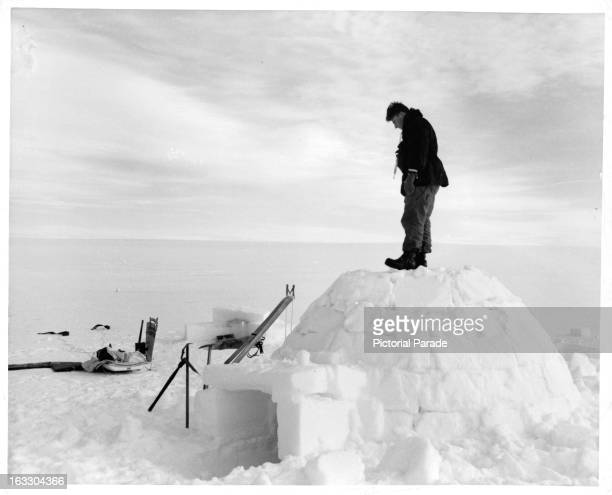 A man is standing on an igloo in the near and far distance there is snow for miles and miles in Greenland 1953