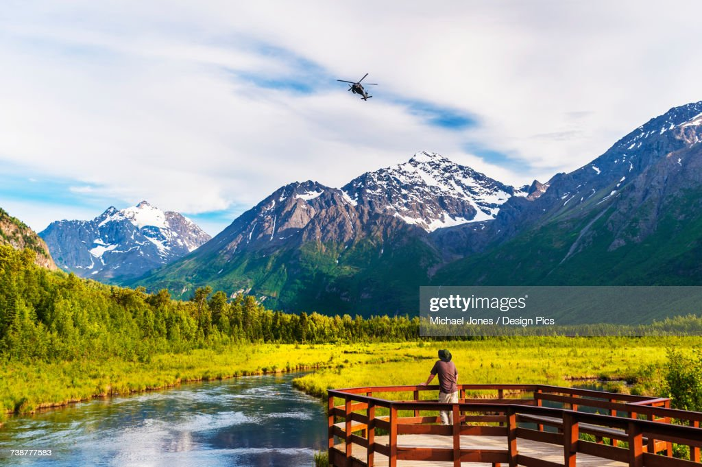 A man is standing on the Eagle River Nature Center boardwalk while a Black Hawk helicopter flies over head in the Chugach State Park in Southcentral Alaska, USA : Stock Photo