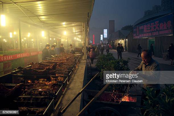 Man is stoking the fire at an outdoor BBQ in front of a restaurant in downtown Chongqing. This image was taken near the Huaxinjie subway station.