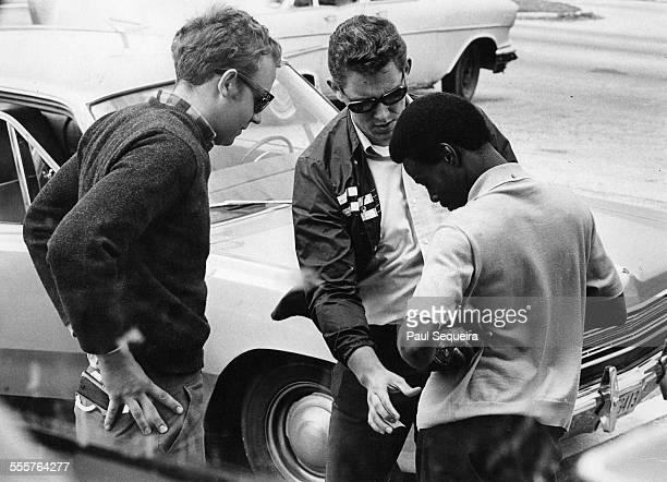 A man is stopped and frisked by nonuniformed police officers on Roosevelt Road Chicago Illinois 1970s