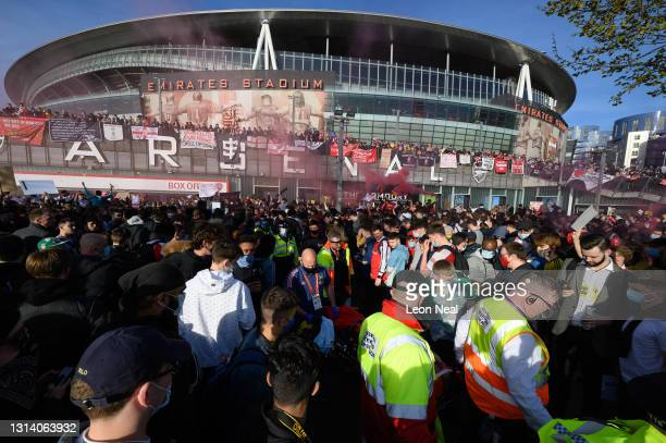 Man is stretchered through the crowd after falling from an awning onto his head during a protest against the club's owner Stan Kroenke ahead of the...