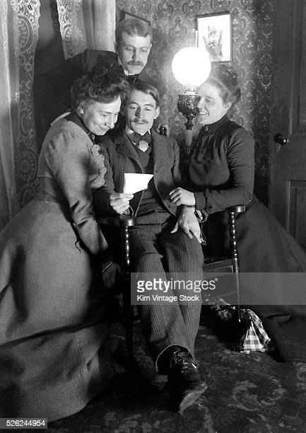 Man is surrounded as he reads a note, ca. 1900