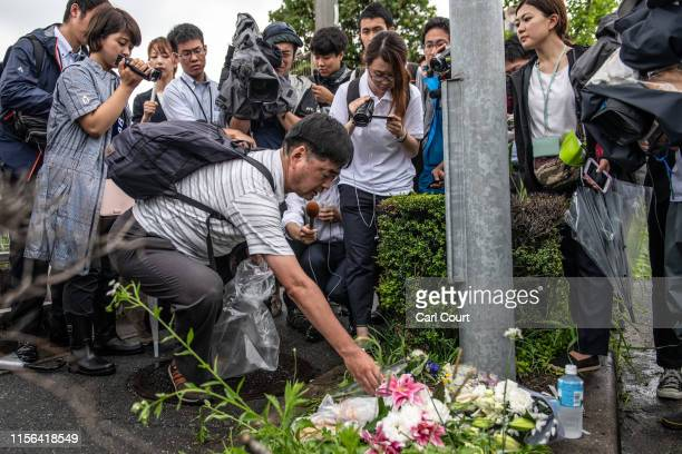 Man is surrounded by members of the media as he lays flowers near the Kyoto Animation Co studio building following an arson attack on July 19, 2019...