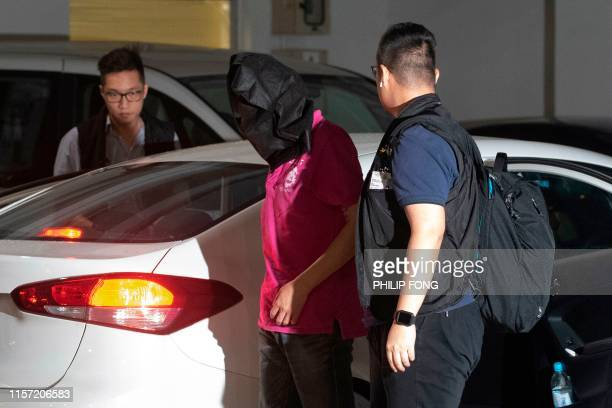 A man is taken away by police after he was arrested for illegal assembly in the district of Yuen Long in Hong Kong on July 22 where there was a...