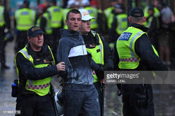 Man is taken away by police officers after protesters supporting the Black Lives Matter movement clash with opponents in central London on June 13 in...