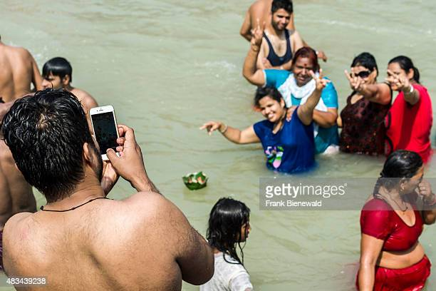 HARIDWAR UTTARAKHAND INDIA A man is taking a photograph with his mobile phone of his family bathing at Harki Pauri Ghat at the holy river Ganges