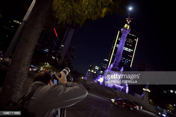 A man is taking pictures of the Super Moon during the start of the total lunar eclipse at the Angel de la Independencia in Mexico City on January 20...