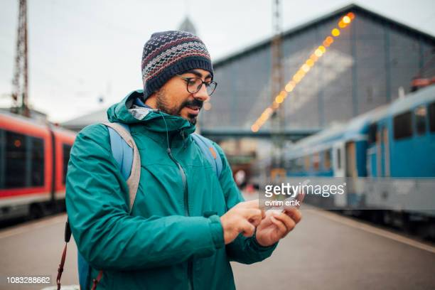 man is texting at train station - hungary stock pictures, royalty-free photos & images