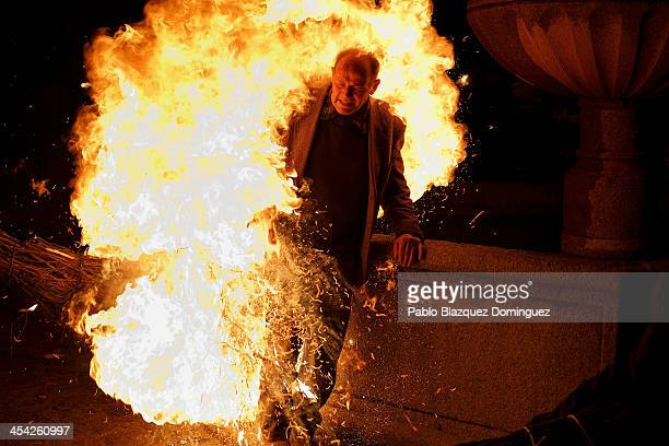 A man is touched by the flames of a burning broom during 'Los Escobazos' Festival on December 7 2013 in Jarandilla de la Vera Spain Although the...