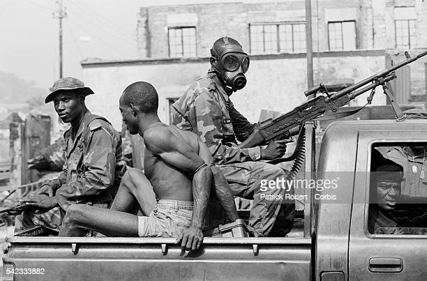 A man is transported by truck after being arrested by soldiers from ECOMOG the West African intervention force