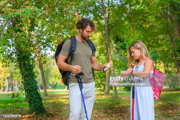 man is traveling in the forest with his little girl and facing a mosquitoes. - insect bites images stock pictures, royalty-free photos & images