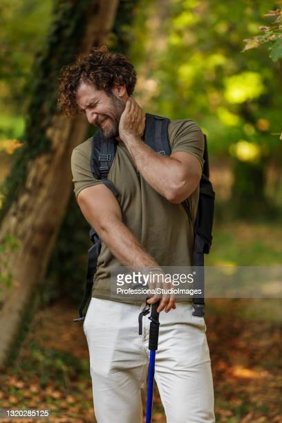 man is traveling with backpack and has problems with insects in the forest. - insect bites images stock pictures, royalty-free photos & images