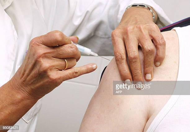 A man is vaccinated against swine flu in Burgos' health center northern Spain on November 16 2009 Spain launched a vaccination campaign against swine...