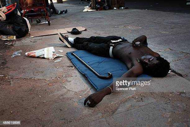 Man is viewed sprawled on the ground in an area which has witnessed an explosion in the use of K2 or 'Spice', a synthetic marijuana drug, in East...