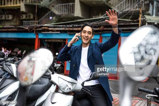 Homme attend au stationnement de scooter de moteur à Taipei - renonciation à des amis à venir