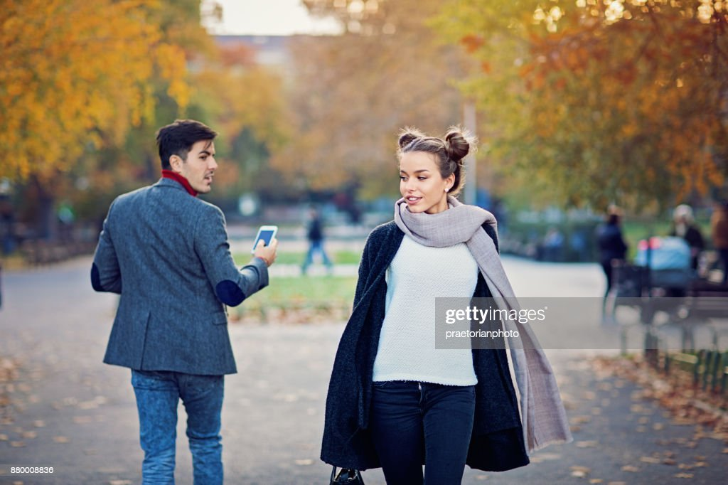 Man is walking in the city and turning around a beautiful girl : Stock Photo