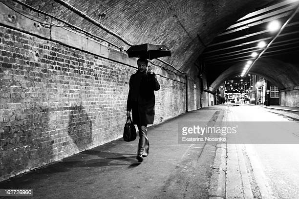 Man is walking under railway bridge at Southwark under his umbrella on a rainy evening. London, December 2010