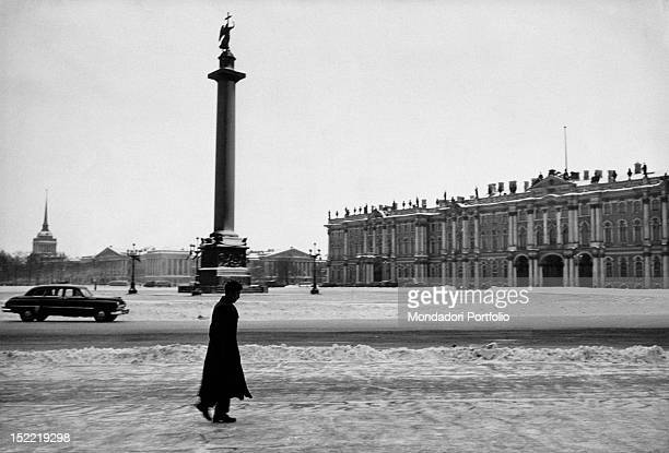 A man is walking with his hands in the pockets of his coat on the snow covering the Palace Square where dominate the Alexander Column and the Winter...
