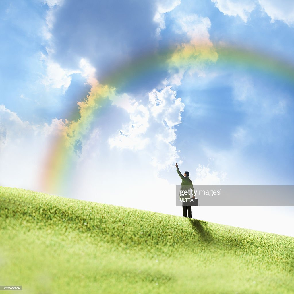 A man is waving his hand under a rainbow.  : Stock Photo