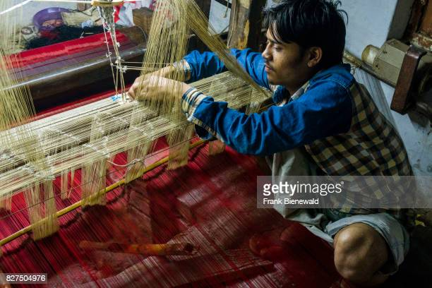 A man is weaving silk material at a old fashion handloom in a factory in the suburb Godowlia