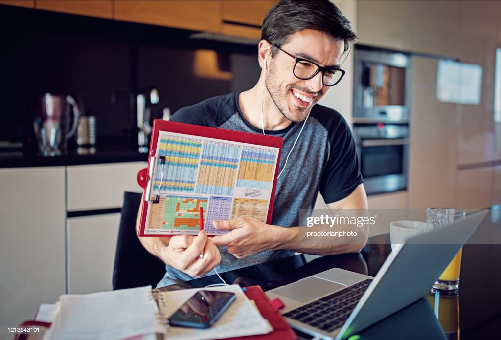 Man is working at home and video conferencing using his laptop : Stock Photo