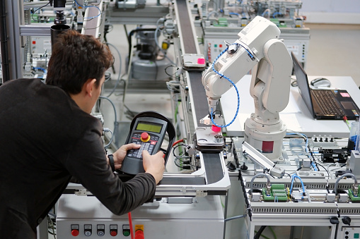 Man is working to control a robotic arm 1183043211