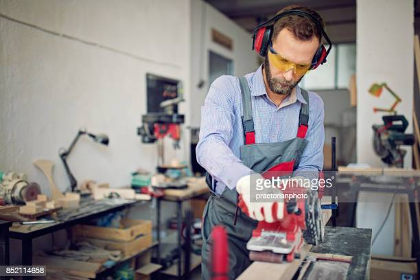 Man is working with sander in small family carpenter factory