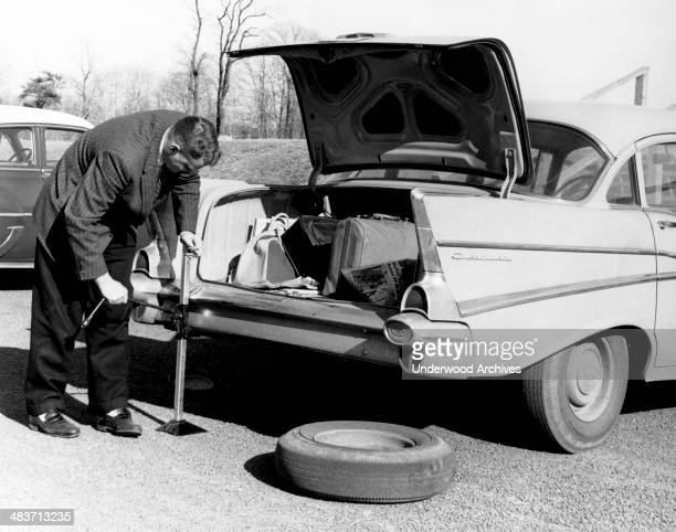 A man jacking up his 1957 Chevrolet to change a rear tire on it 1958