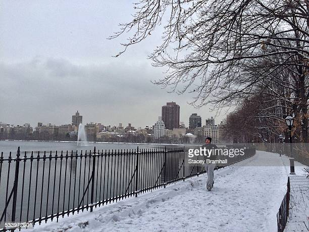 Man jogging around the Reservoir in New York City's Central Park on a snowy winter day.