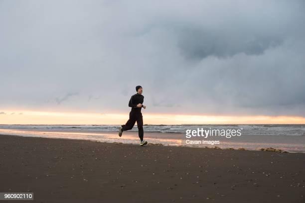 man jogging at beach against cloudy sky - homens de idade mediana - fotografias e filmes do acervo