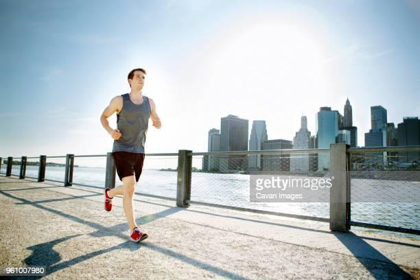 man jogging at riverbank against sky on sunny day - homens de idade mediana - fotografias e filmes do acervo
