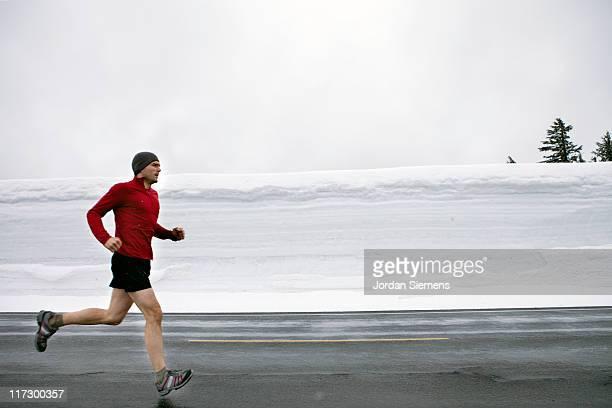 man jogging down road with heavy snow. - ランニングショートパンツ ストックフォトと画像