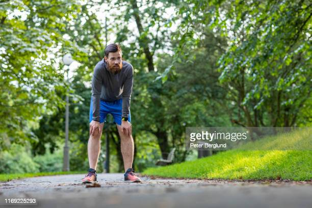 man jogging in a park - hand on knee stock pictures, royalty-free photos & images
