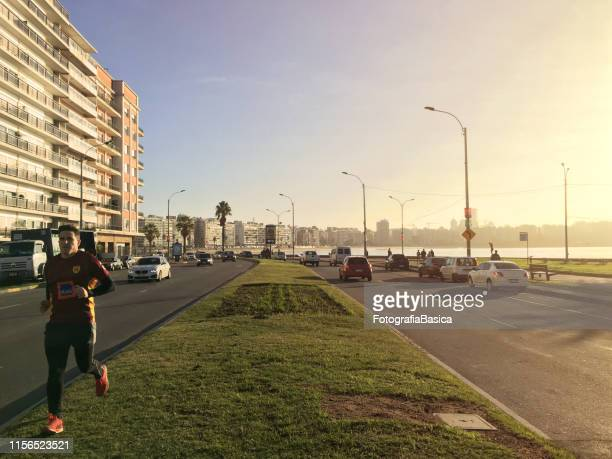 man jogging in coastal boulevard - boulevard stock pictures, royalty-free photos & images