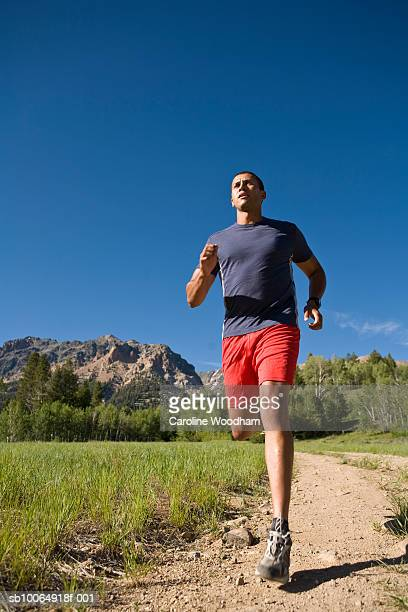 man jogging in mountain landscape, low angle view - number of people stock pictures, royalty-free photos & images