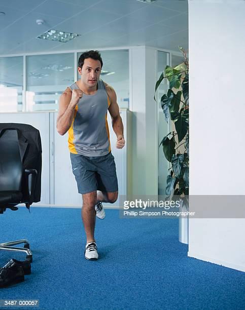 man jogging in office - ランニングショートパンツ ストックフォトと画像