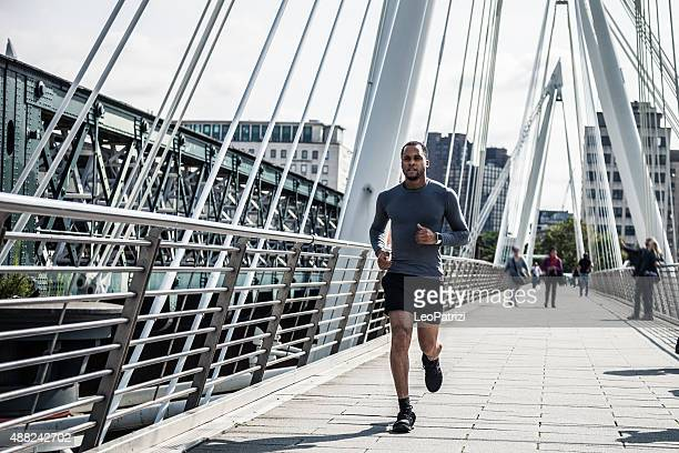 Man jogging on a modern bridge