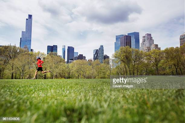 man jogging on grassy field at park against city - center athlete stock pictures, royalty-free photos & images