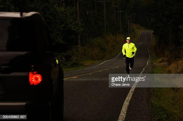 Man jogging on road, car approaching, dusk