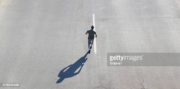 Man jogging on road, copy space