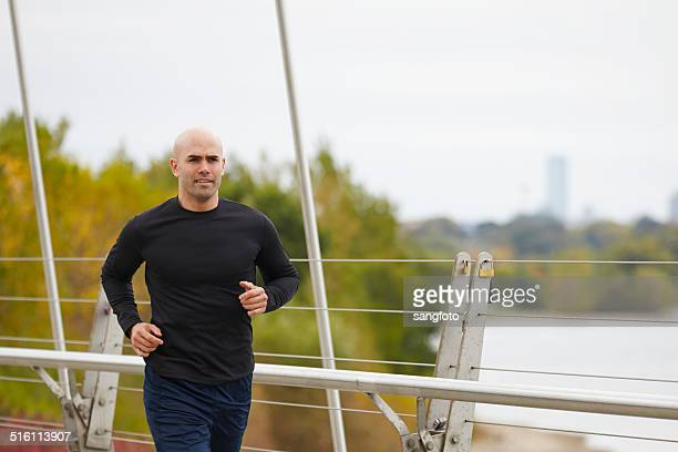 man jogging on the bridge in autumn city - long sleeved stock photos and pictures