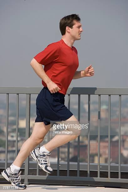 Man jogging on urban sidewalk