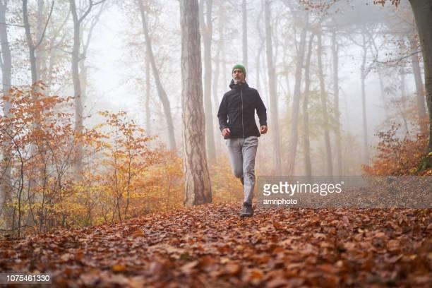 Mann an kalten nebligen Tag im Freien in Wutumn Wald joggen