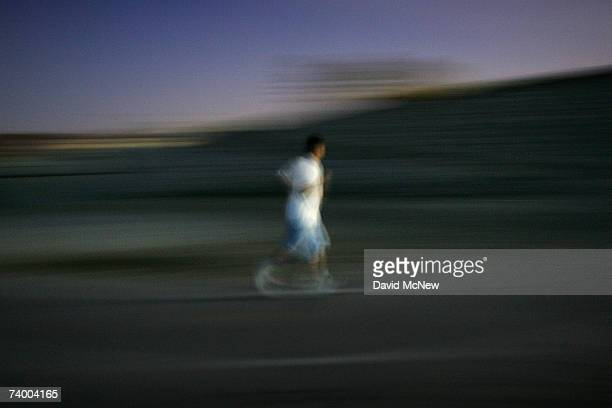 A man jogs at night along the San Gabriel River where the mosquitoes that can carry West Nile Virus are believed to have bred in previous seasons on...